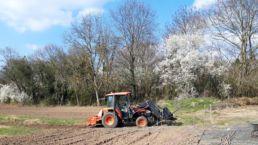 Traktor pflügt auf dem Freilandacker der Orangerie Aukamm